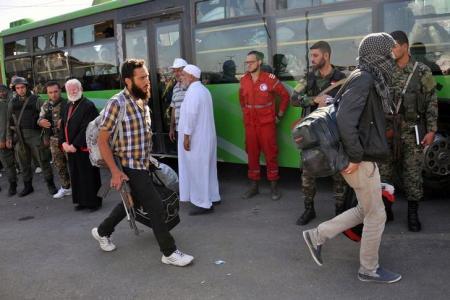 بدء خروج مقاتلين سوريين وعائلاتهم من حي الوعر بعد اتفاق مع الحكومة