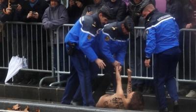 ناشطة عارية الصدر تخترق موكب الرئيس الأمريكي ترامب في باريس (صور)