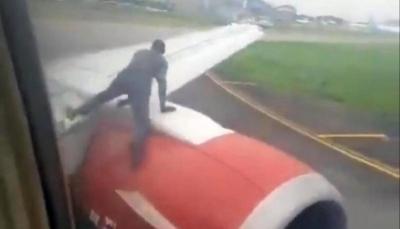 رجل يتسلق جناح طائرة قبل لحظات من إقلاعها (فيديو)